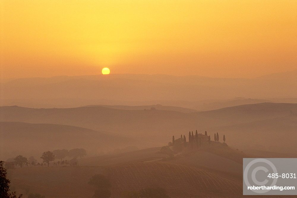 Landscape of fields and cypress trees at sunset in the hills of Tuscany, Italy