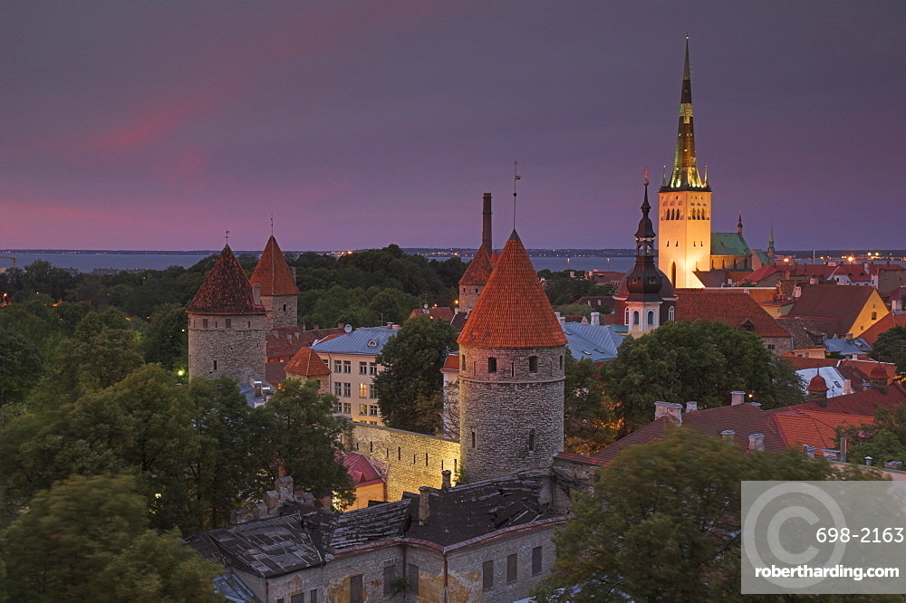 Medieval town walls, defence towers and spire of St. Olav's church at sunset, Tallinn, Estonia, Baltic States, Europe