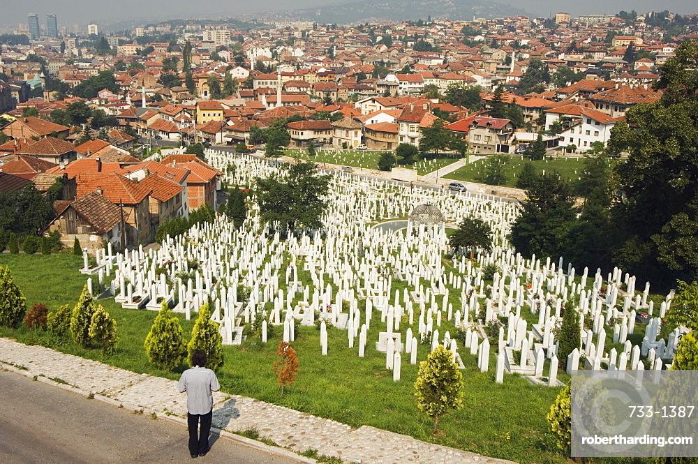 Man reflecting at cemetery overlooking city houses, Sarajevo, Bosnia, Bosnia-Herzegovina, Europe
