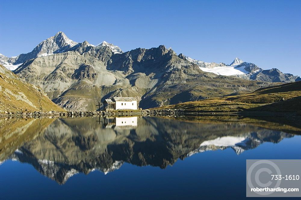 Perfect reflection in lake at Schwarzee Paradise, and small mountain hut, Zermatt Alpine Resort, Valais, Switzerland, Europe