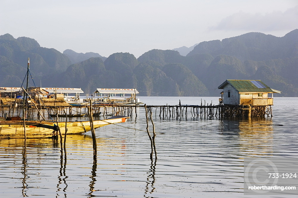 Unusual shaped coastal hills of Coron Island, and stilt houses, Coron Town, Busuanga Island, Palawan Province, Philippines, Southeast Asia, Asia