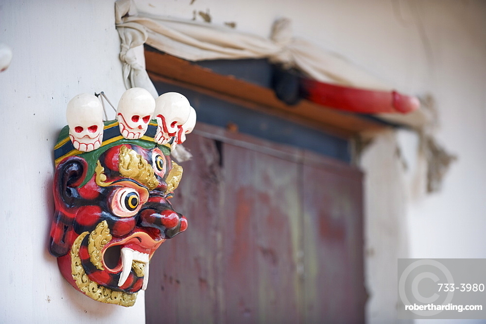 Mask and phallus hanging on a door to protect its occupants, near the temple of the Divine Madman, Metshina, Punakha, Bhutan