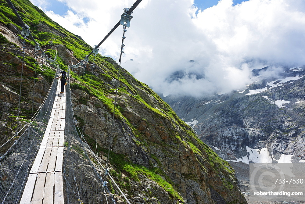 Hiker on a suspension bridge, Chamonix, Rhone Alpes, Haute Savoie, France, Europe