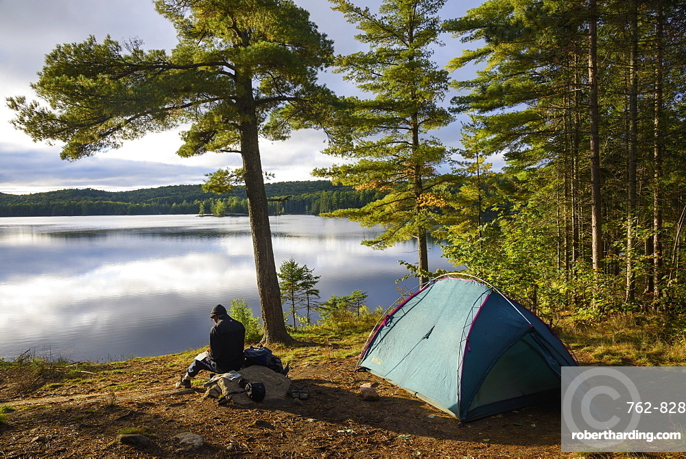 Hiker camping by Provoking Lake in Algonquin Provincial Park, Ontario, Canada, North America