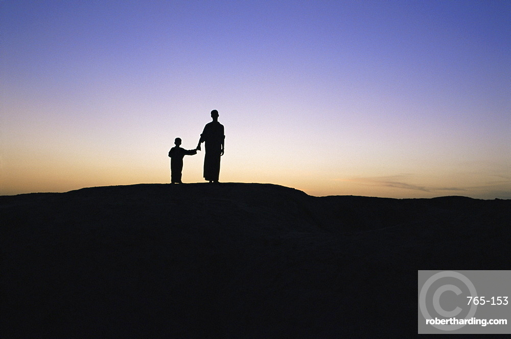 Silhouette of two people at the archaeological area, Kish, Iraq, Middle East