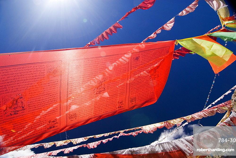 Red prayer flags against blue sky, Yushu, Qinghai, China, Asia