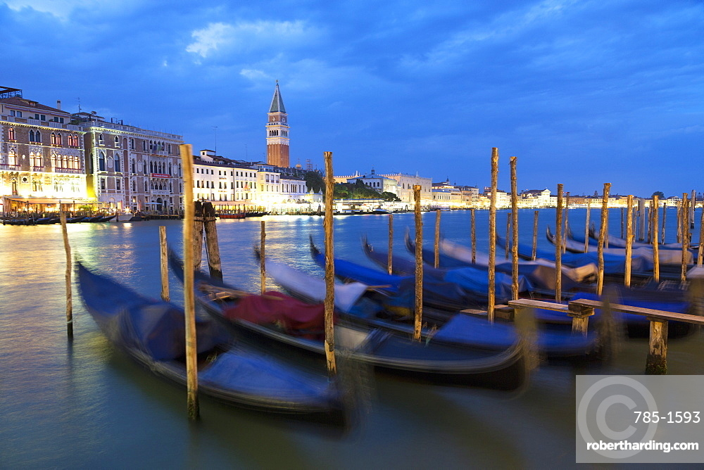 Gondolas moored at night at Campo della Salute on the Grand Canal with St. Mark's Campanile in the distance, Venice, UNESCO World Heritage Site, Veneto, Italy, Europe