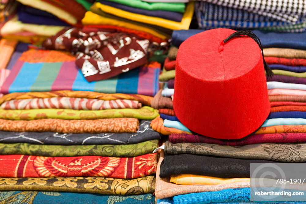 Colourful cotton fabric and a traditional fez for sale in a shop in Luxor, Egypt, North Africa, Africa