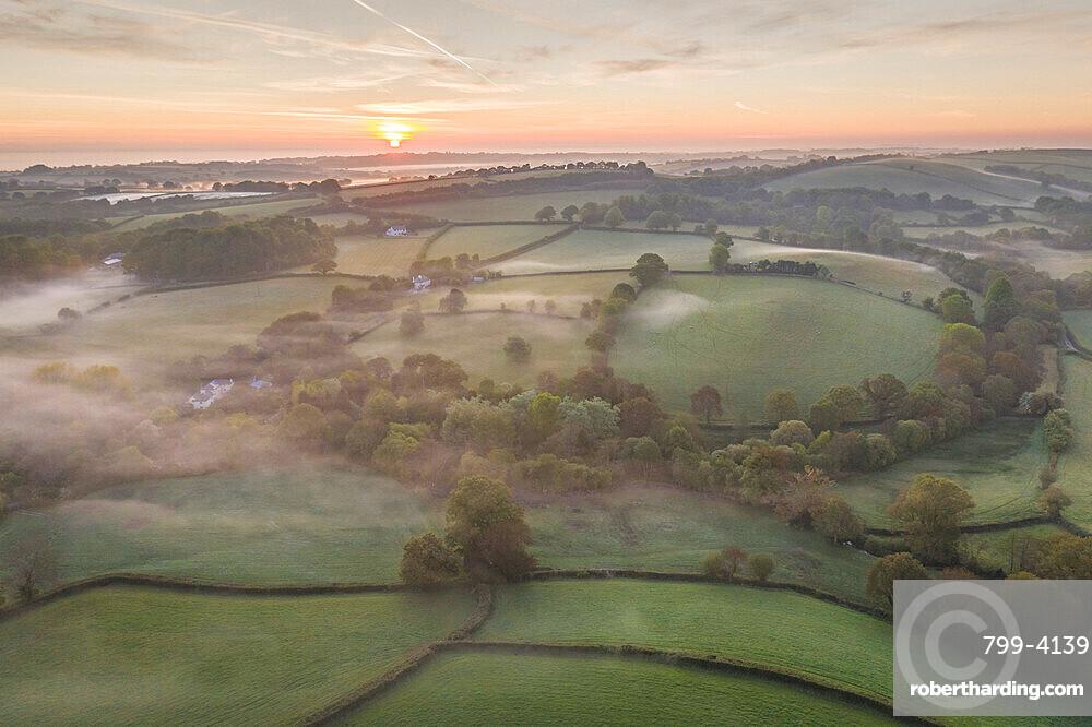 Misty spring sunrise over rolling countryside, South Tawton, Devon, England, United Kingdom, Europe
