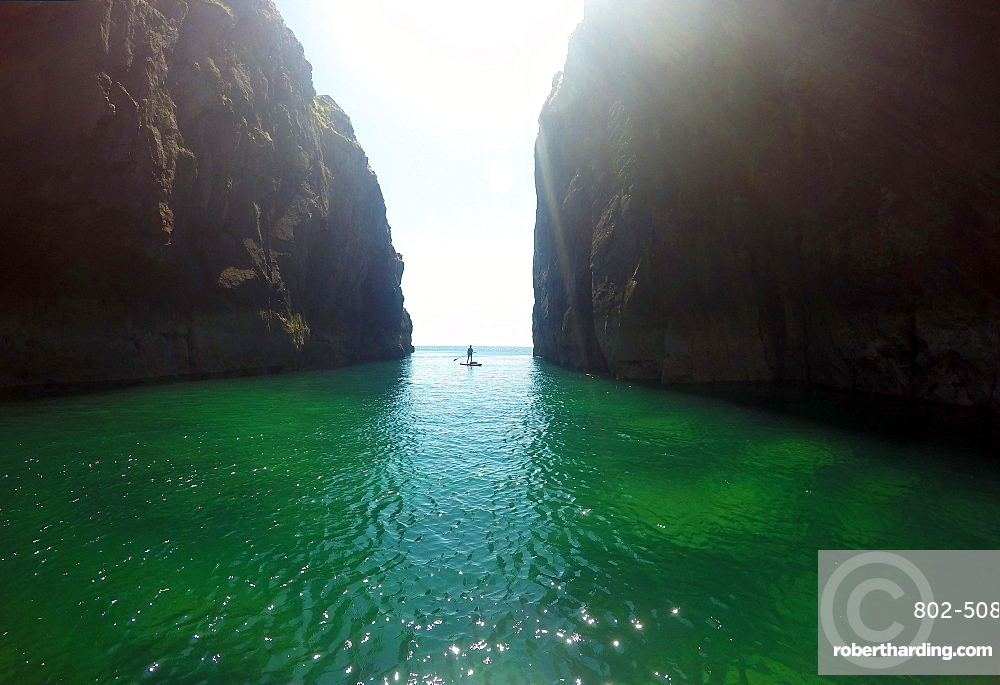 Paddle boarder exploring cliffs and rock architecture on the Pembrokeshire Coast, Wales, United Kingdom, Europe