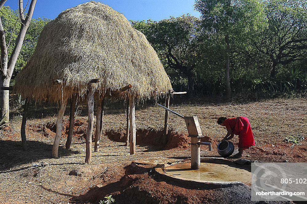 Woman washes water pot before filling it at village pump by elevated haystack, Baliguda district, Orissa, India, Asia