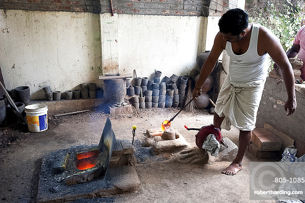 Man in white vest and dhoti, pouring molten bronze into clay mould, in Chola style lost wax bronze casting workshop, Thanjavur, Tamil Nadu, India, Asia