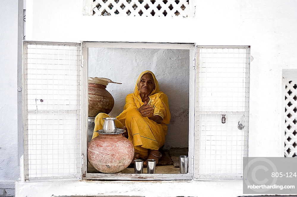 Woman offering drinking water to devotees at Jagdish temple, Udaipur, Rajasthan, India, Asia