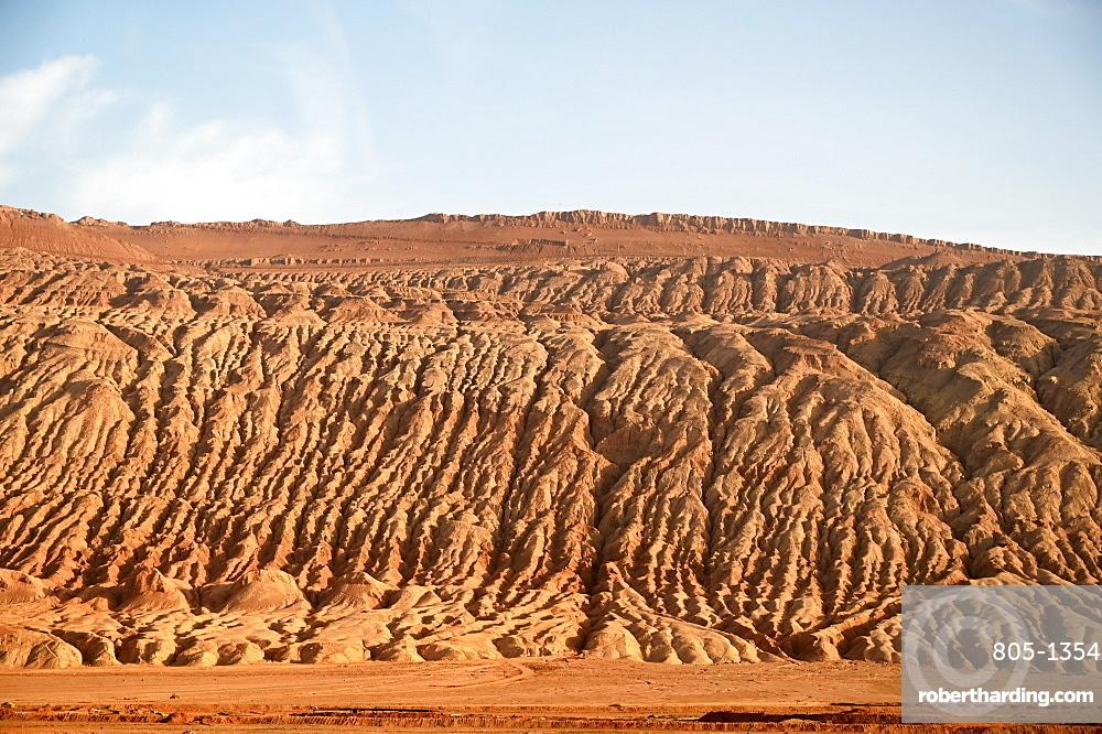 Buildings dwarfed by vast Gobi desert landscape along the Silk Road near Turfan, Xinjiang, China, Asia