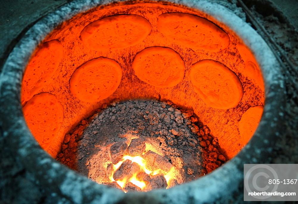 Flatbreads cooking in flatbread oven in Turfan street night market, Turfan, Xinjiang, China, Asia