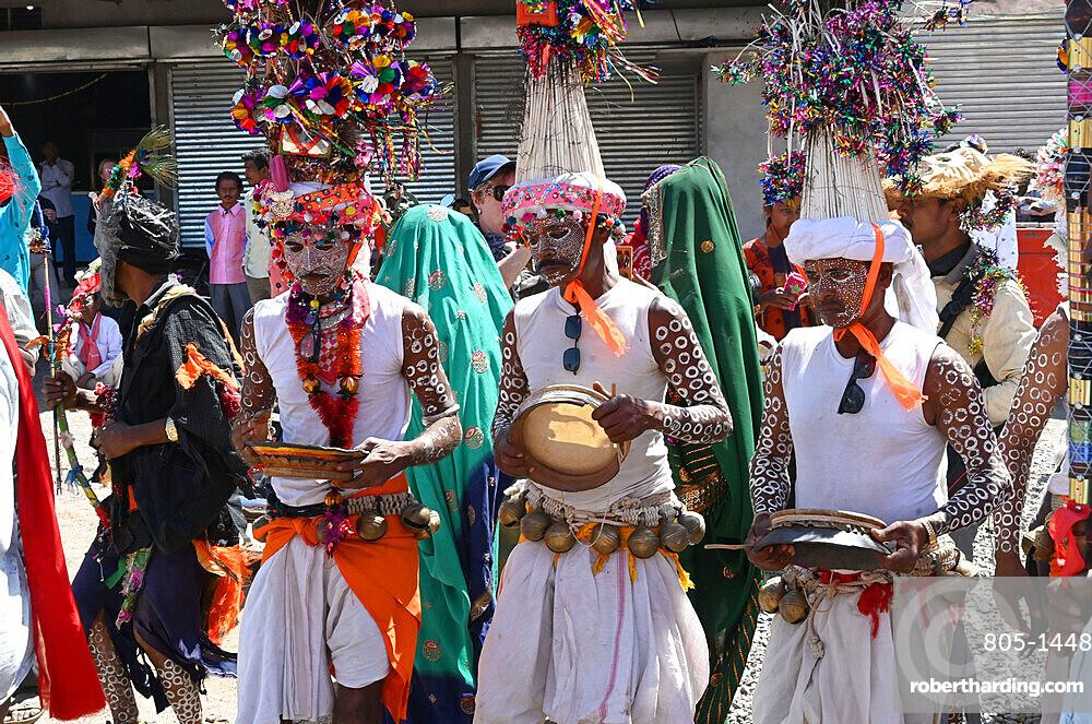 Adivasi tribal men, faces and bodies decorated, wearing ornate headgear, dancing to celebrate Holi festival, Kavant, Gujarat, India, Asia
