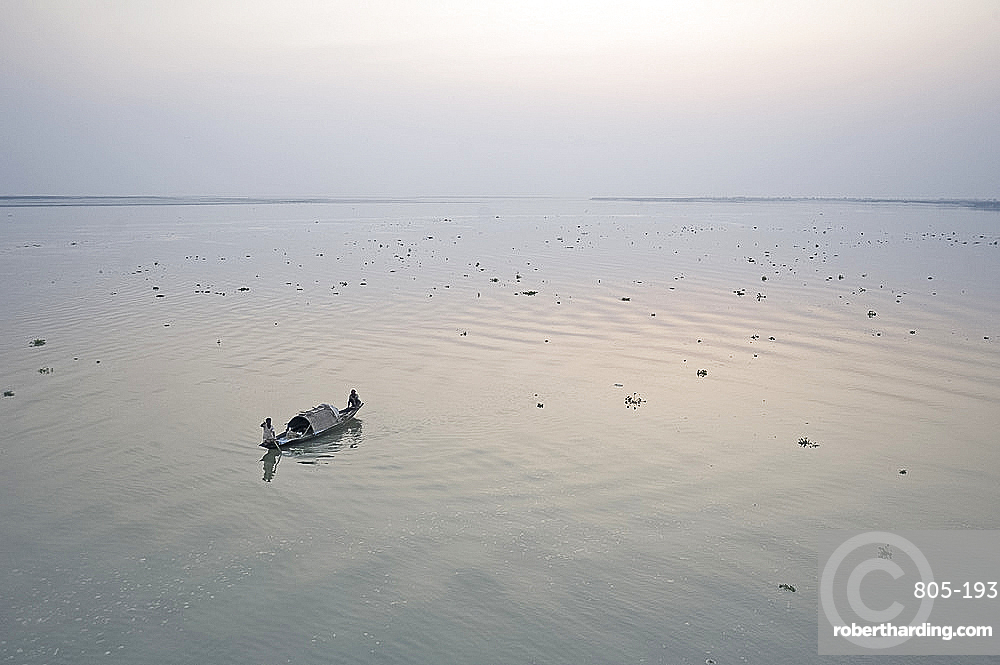 Two fisherman on boat at dawn on the Brahmaputra River, Assam, India, Asia