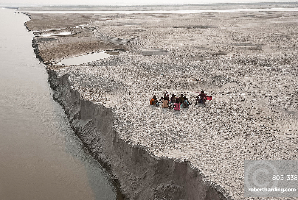 Villagers stopping to eat near the fragile edge of a sandspit in the River Ganges, Sonepur, Bihar, India, Asia
