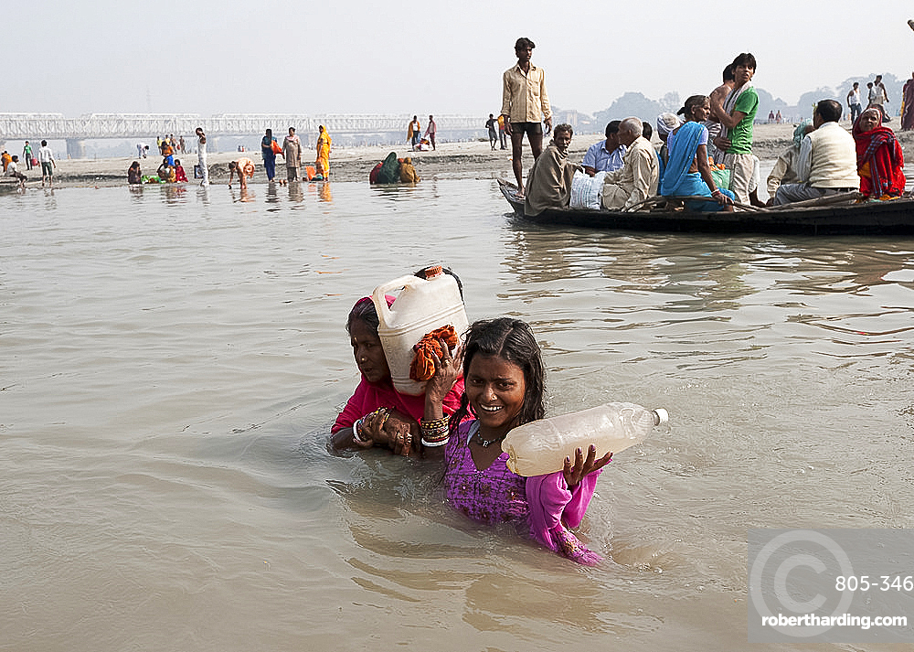 Mother and daughter wading across the River Ganges holding bottles of Holy River Ganges water, Sonepur, Bihar, India, Asia