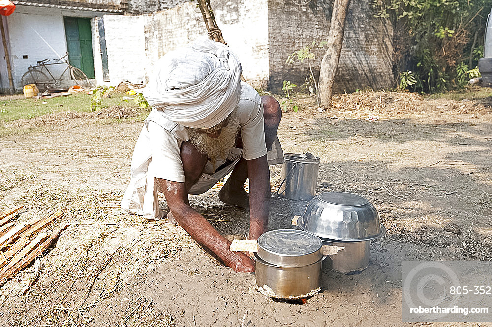 Bihari man in white turban and dhoti, making clay oven in the ground to cook his meal at Sonepur Cattle Fair, Bihar, India, Asia