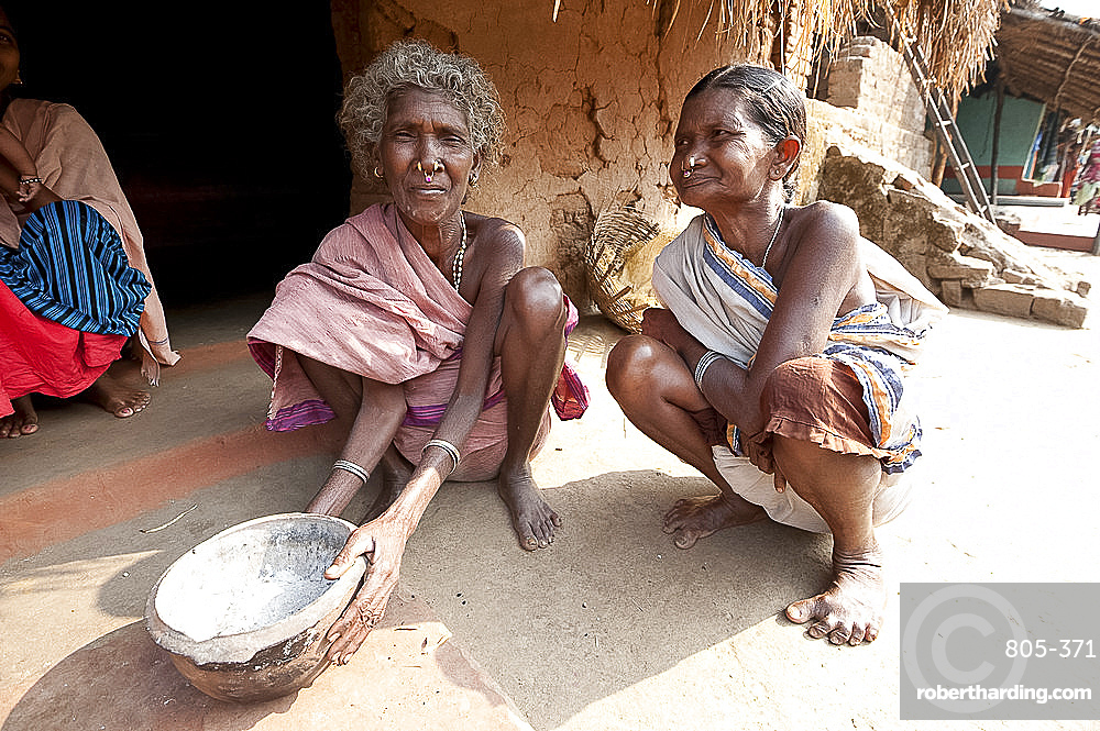 Two Desia Kondh tribal women squatting outside their village house holding welcome bowl of ash, Bissam Cuttack, Orissa, India, Asia