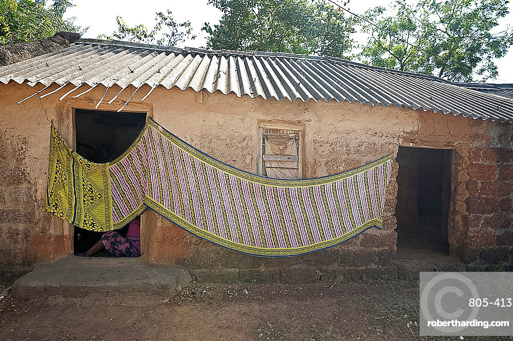 Cotton sari being hung out to dry across village house wall, rural Orissa, India, Asia