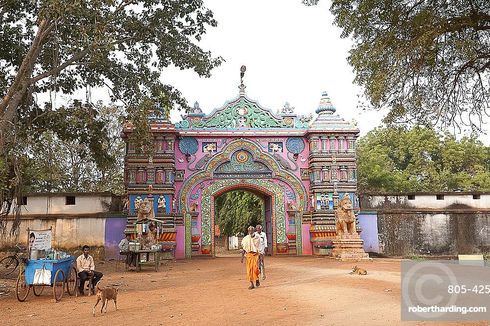 Ascetics walking through ornately carved and painted entrance to Joranda monastery complex, Joranda, Orissa, India, Asia