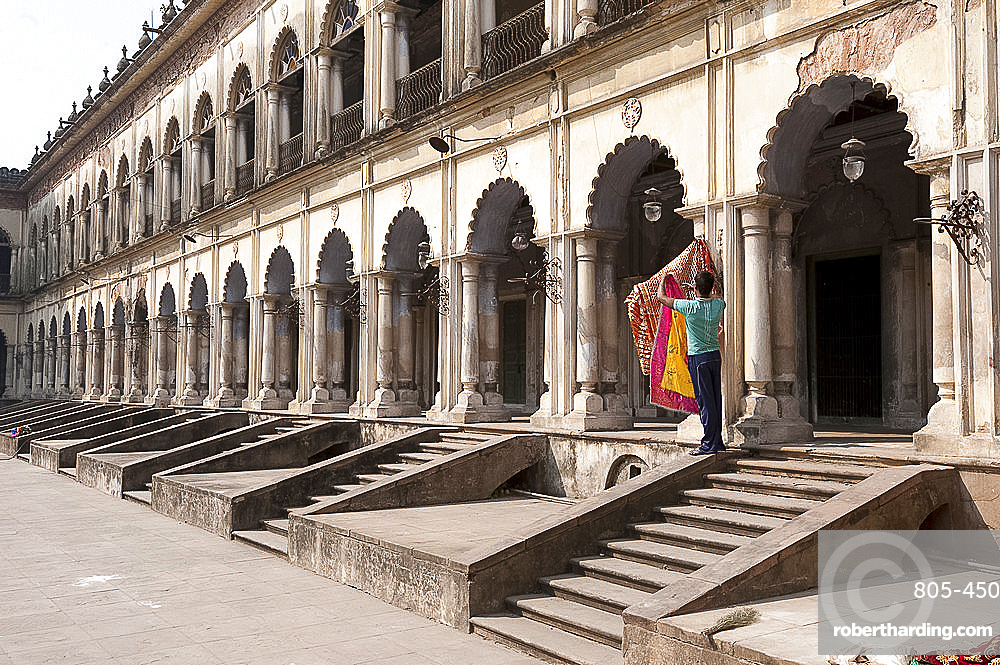 Man hanging out washed Quran cover cloths outside arched madrasa rooms in the Hugli Imambara, Hugli, West Bengal, India, Asia