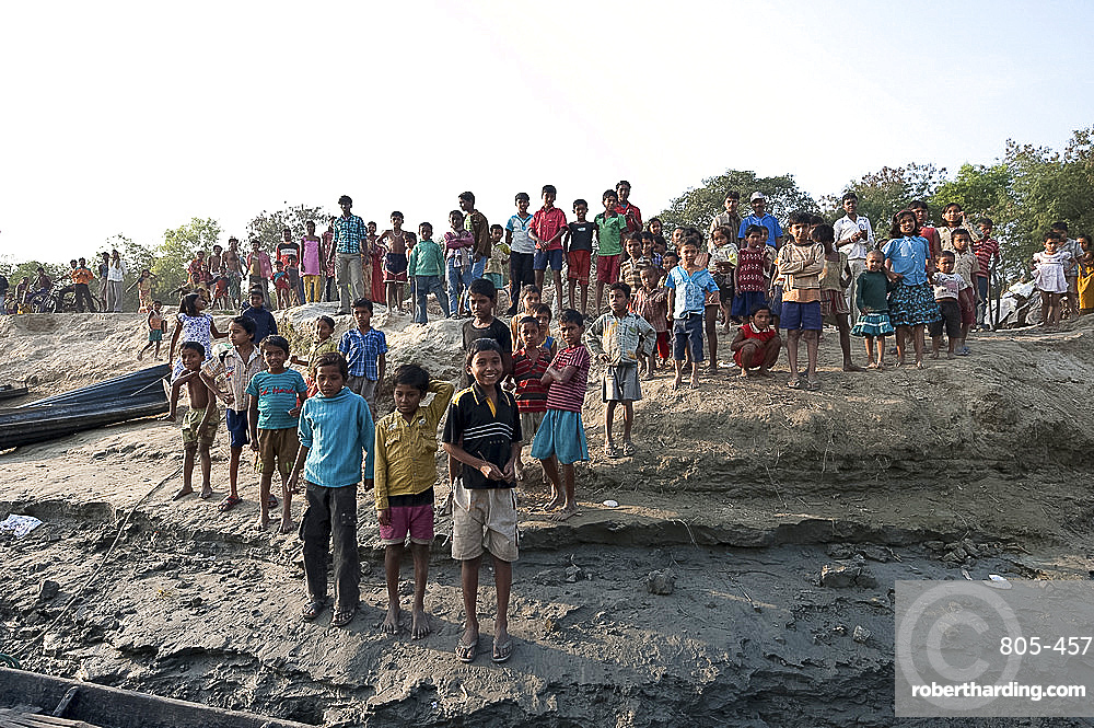 Villagers waiting on the riverbank of the River Hugli to welcome visitors arriving by boat, rural West Bengal, India, Asia