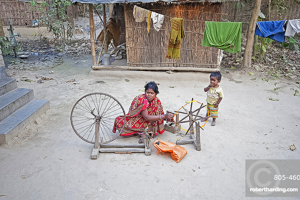 Woman spinning silk on home made spinning wheel made from wood and bicycle wheel, in rural village, West Bengal, India, Asia
