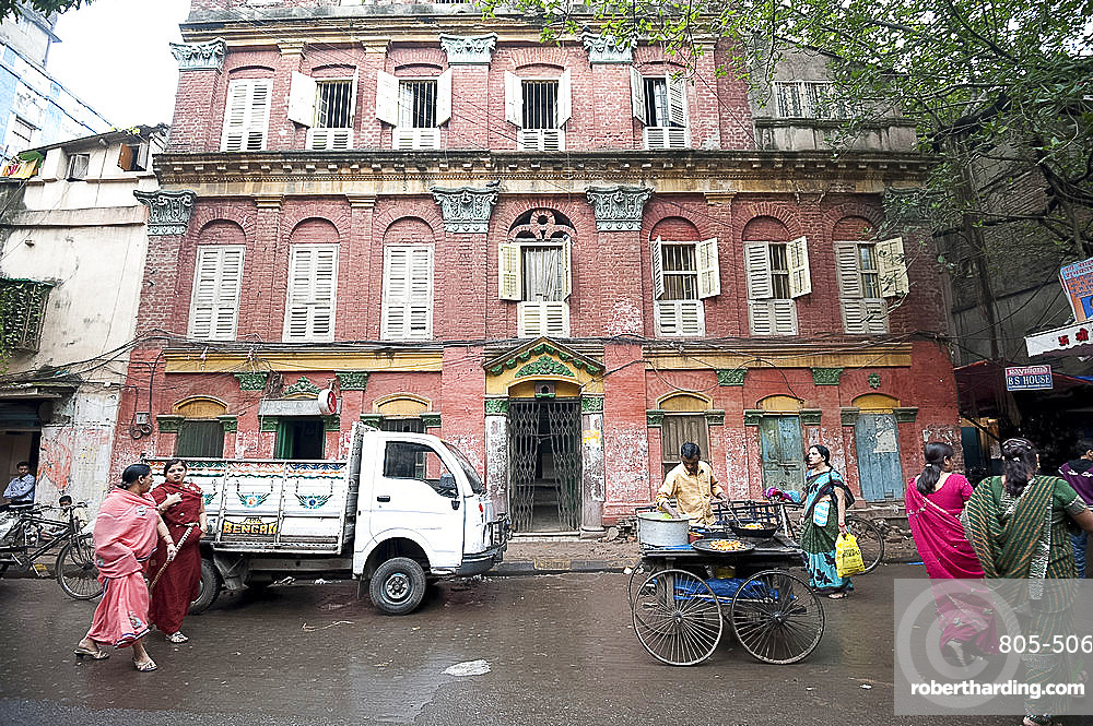 Street snack seller with his wheeled stall outside beautiful old Raj era building in Kolkata back street, West Bengal, India, Asia