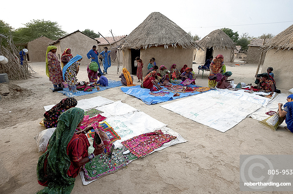 Pathan village people, women showing their traditional embroideries in front of mud and thatched tribal houses, Jarawali, Kutch, Gujarat, India, Asia
