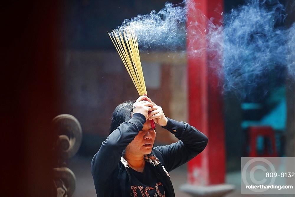 Taoist temple, Emperor Jade pagoda (Chua Phuoc Hai), Taoist worshipper burning incense sticks, Ho Chi Minh City, Vietnam, Indochina, Southeast Asia, Asia