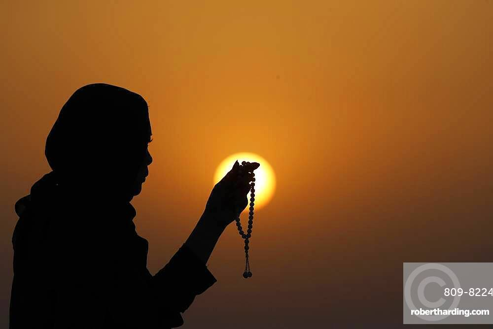 Silhouette of a Muslim woman holding prayer beads in her hands and praying at sunset, United Arab Emirates, Middle East