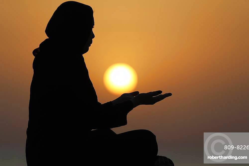 Silhouette of a Muslim woman in abaya praying with her hands at sunset, United Arab Emirates, Middle East