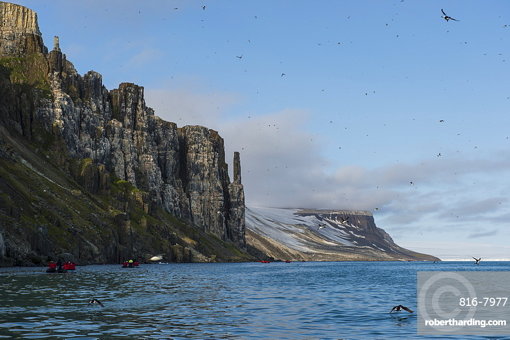 Tourist in zodiacs looking at cliffs of Alkerfjellet with thousands of kittywakes, Svalbard, Arctic