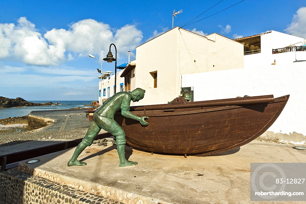 Boat with statues of fishermen at the old harbour in this north west coast village, El Cotillo, Fuerteventura, Canary Islands, Spain, Atlantic, Europe