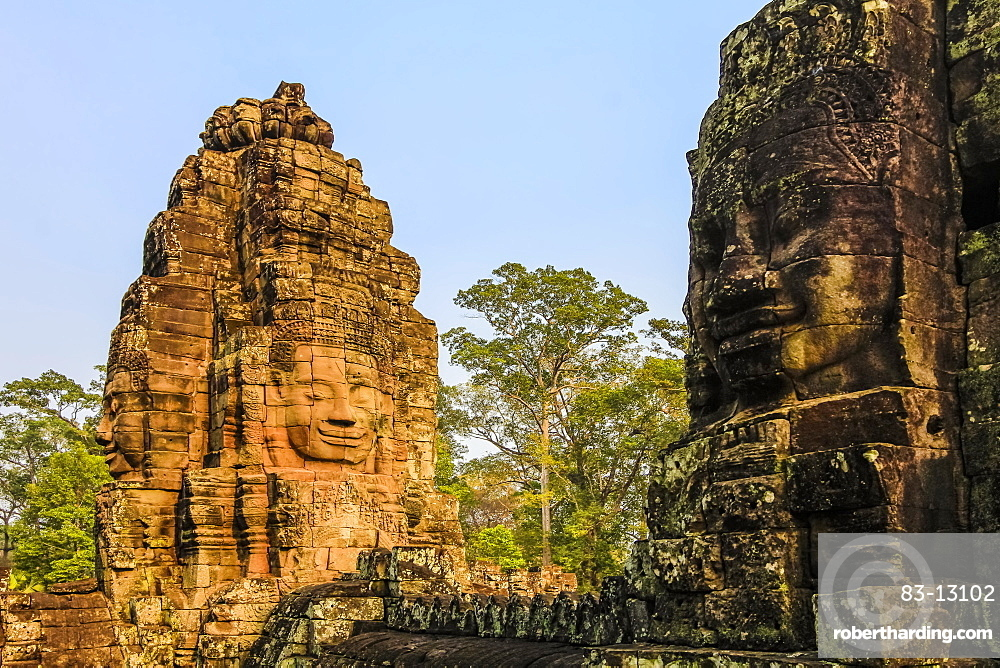 Towers and three of the 216 smiling sandstone faces at 12th century Bayon temple in Angkor Thom walled city, Angkor, UNESCO World Heritage Site, Siem Reap, Cambodia, Indochina, Southeast Asia, Asia