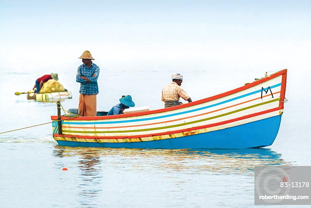 Fishermen in colourful boat on the Arabian Ocean just off popular Marari Beach, Mararikulam, Alappuzha (Alleppey), Kerala, India, Asia