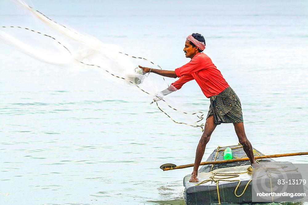 Fisherman casting weighted net on small raft offshore of popular Marari Beach, Mararikulam, Alappuzha (Alleppey), Kerala, India, Asia