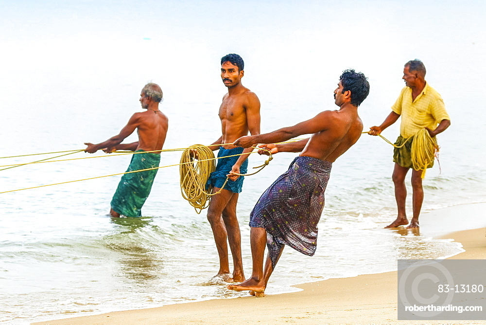Fishermen pulling large set net to shore at busy, popular Marari Beach, Mararikulam, Alappuzha (Alleppey), Kerala, India, Asia