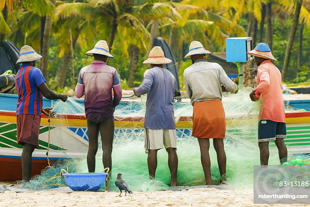 Fishermen cleaning and folding gill nets at busy, popular Marari Beach, Mararikulam, Alappuzha (Alleppey), Kerala, India, Asia