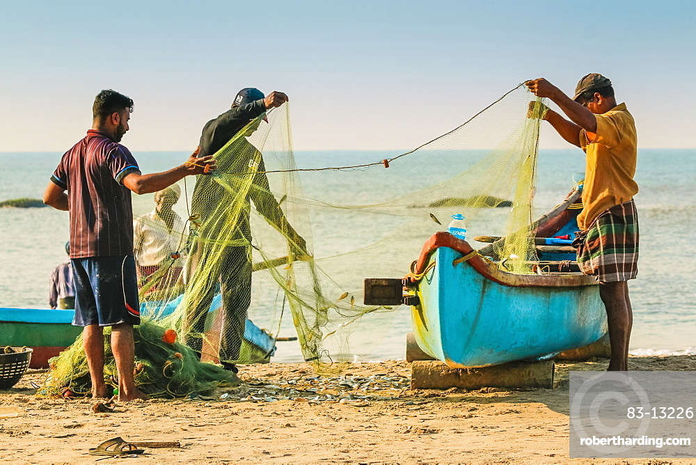 Fishermen cleaning net at beautiful Kizhunna Beach, south of Kannur on the Keralan north coast, Kizhunna, Kannur, Kerala, India, Asia