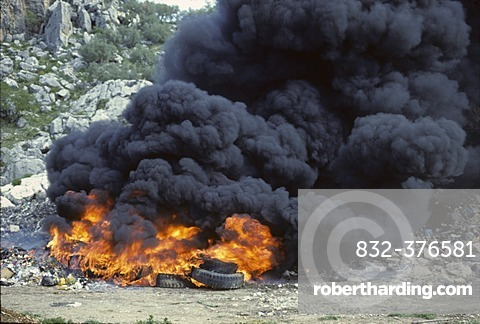 Fire in waste dump with car tires - smoke emission Spain