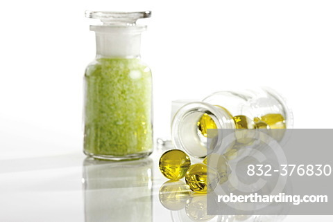 Glass bottles containing golden bath oil beads and green bath salt crystals