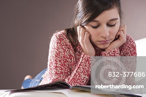 Girl lying on a couch and reading a magazine