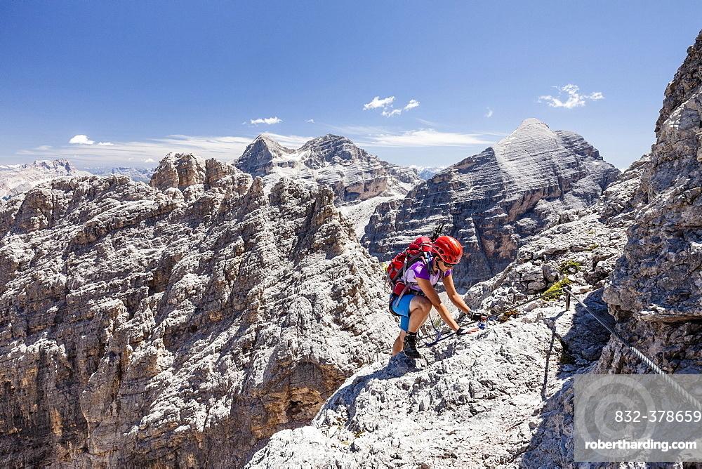 Climber, descent from the Southern Fanesspitze on the Via ferrata Tomaselli, behind the Tofana di Rozes, Tofana di Mezzo and Tofana di Dentro, Dolomites, Alps, Province of Belluno, Italy, Europe