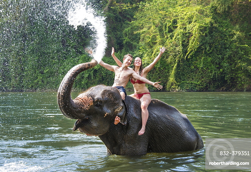 Two teenagers sitting on an Asian Elephant (Elephas maximus), being sprayed with water from the trunk, Kanchanaburi, Thailand, Asia