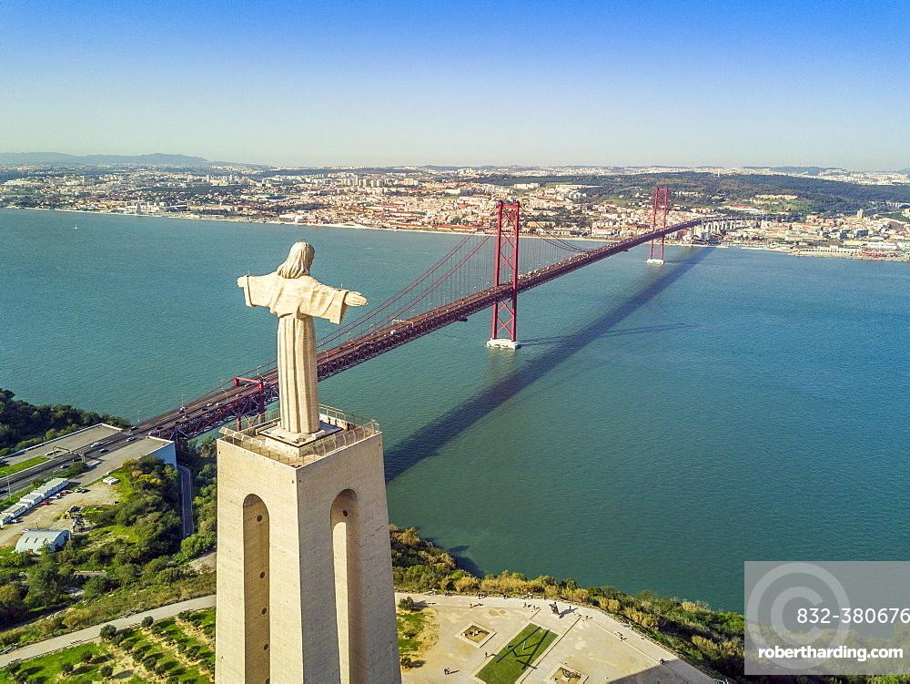 Jesus Christ monument by Tagus river with bridge Ponte 25 de Abril, Lisbon, Portugal, Europe