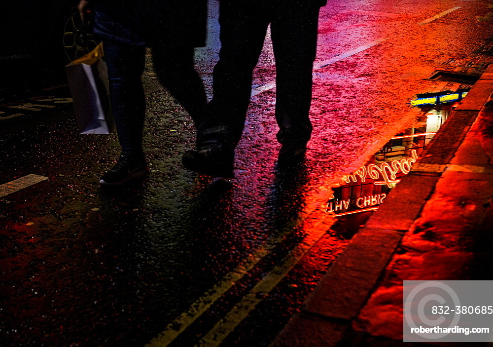 Pedestrians walking on wet road at night, reflection of neon light, West End, London, Great Britain